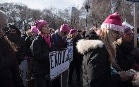 """A woman holds a sign saying """"Enough"""" at Women's March Chicago 2018. The organizers announced a service day in lieu of a march in 2019."""