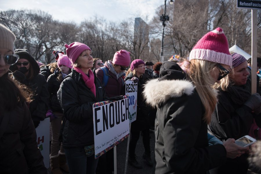 "A woman holds a sign saying ""Enough"" at Women's March Chicago 2018. The organizers announced a service day in lieu of a march in 2019."