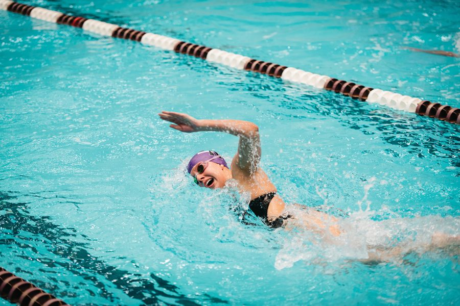 A Northwestern swimmer swims freestyle. The women's team split its matches this weekend in Iowa
