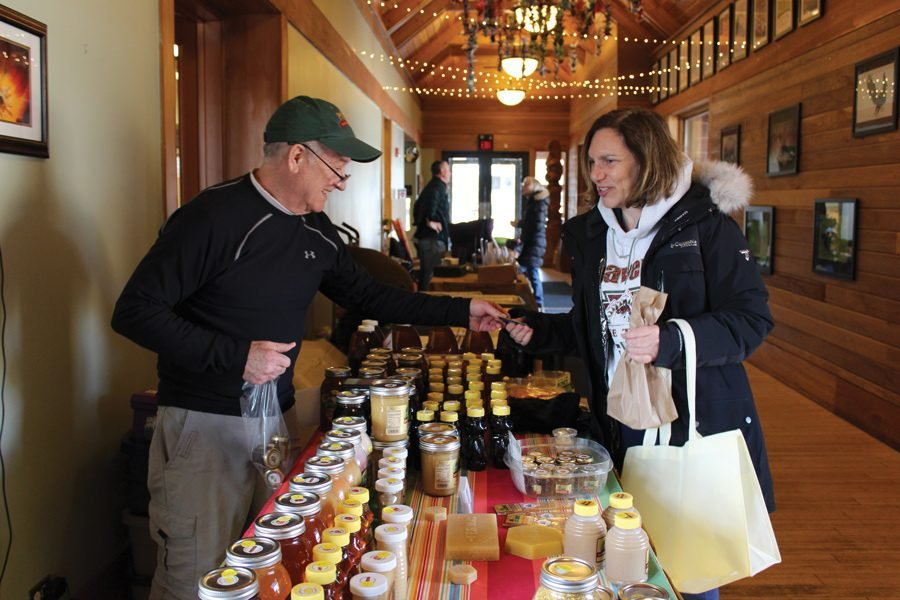John Brandell, owner of Frosty Productions, sells his honey and maple products to customer Ronda Patino. He is a vendor every week at the Evanston Ecology Center Indoor Farmers' Market.