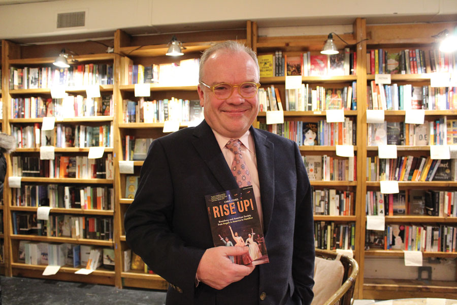 """Chris Jones poses with his book """"Rise Up!"""" at a Bookends & Beginnings event. Jones' book charts works of American theatre that have influenced present-day society like """"Hamilton."""""""
