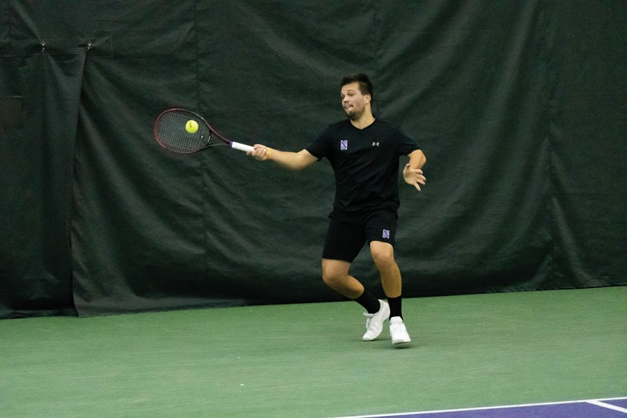 Dominik Stary returns the ball. The junior tennis player has been consistent for the Cats all season.