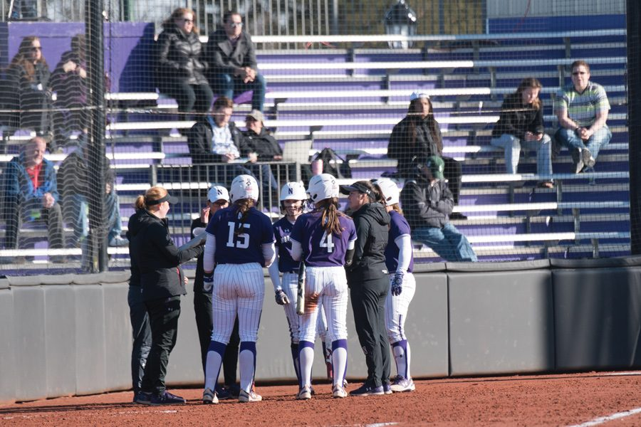 The+team+congregates+at+home+plate.+Northwestern+had+two+freshmen+gain+all-conference+recognition+this+week