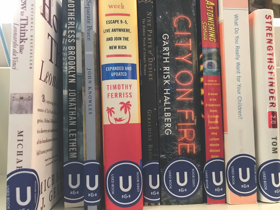"""Used books at Bookends & Beginnings. All used books will sport the navy blue """"U"""" sticker."""