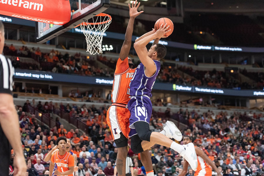 A.J. Turner is met at the rim. Illinois beat Northwestern in the first round of the Big Ten Tournament on Wednesday,