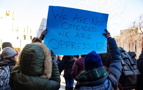 """A student holds up a sign at a February march and teach-in event to protest scientific racism in academia. Activists pushed back against the idea that Satoshi Kanazawa is just """"hurting feelings"""" with his research"""