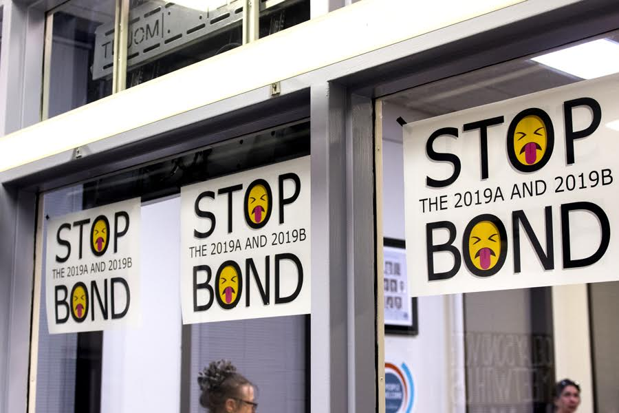 """STOP BOND"" signs plastered across council chambers. Residents protested the bonds authorization at Monday's council meeting."