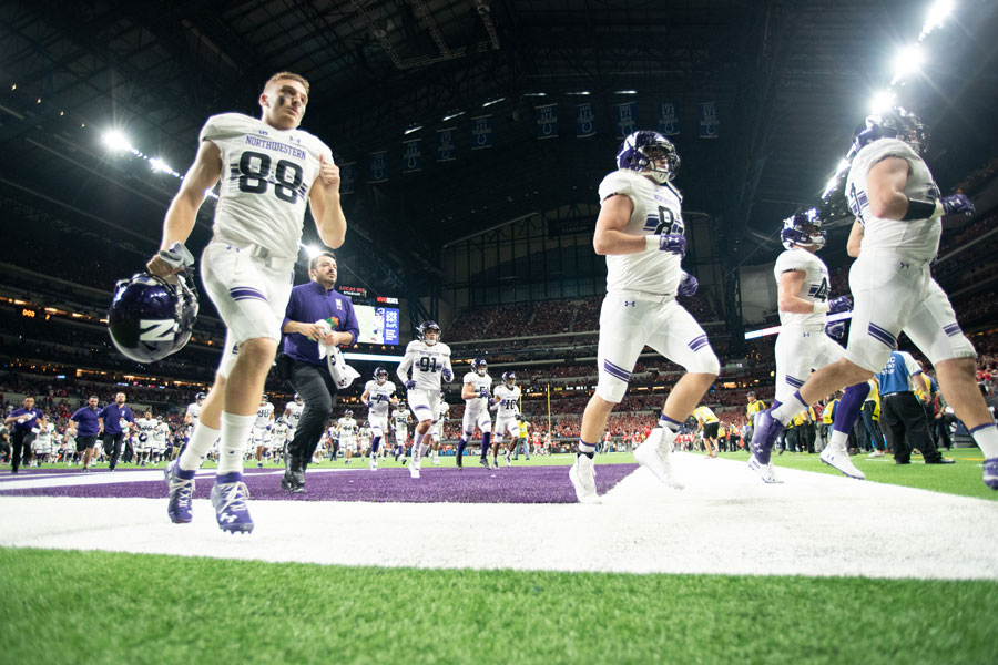 The Cats run out at the 2018 Big Ten Championship Game. Pat Fitzgerald said Saturday that he will not rush to name NU's starting quarterback.