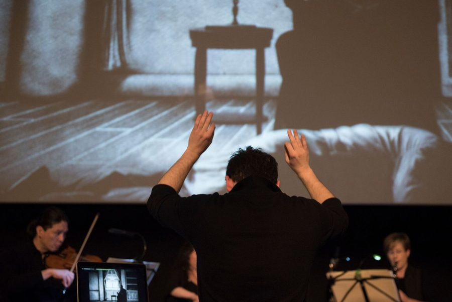 A conductor leads an orchestra at the Sound of Silent Film Festival. The festival commissions composers to write scores for silent films.