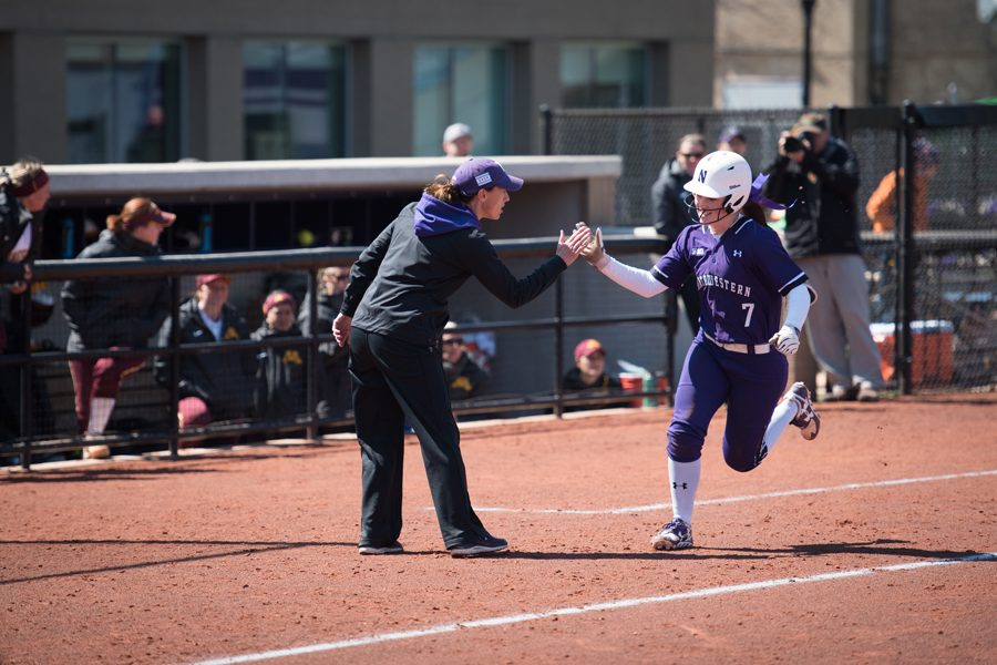 Kate Drohan high-fives Morgan Nelson as she rounds third base. The coach has a chance to earn her 600th career win Tuesday against Notre Dame.