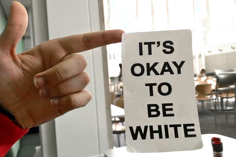 """A sticker found in Allison Dining Hall with the words """"It's okay to be white."""" The phrase has been used in the past by white supremacist groups."""