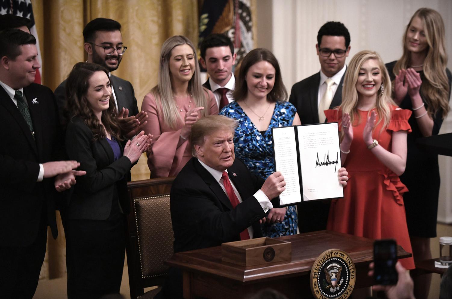 U.S. President Donald Trump holds a signed executive order to require colleges and universities to