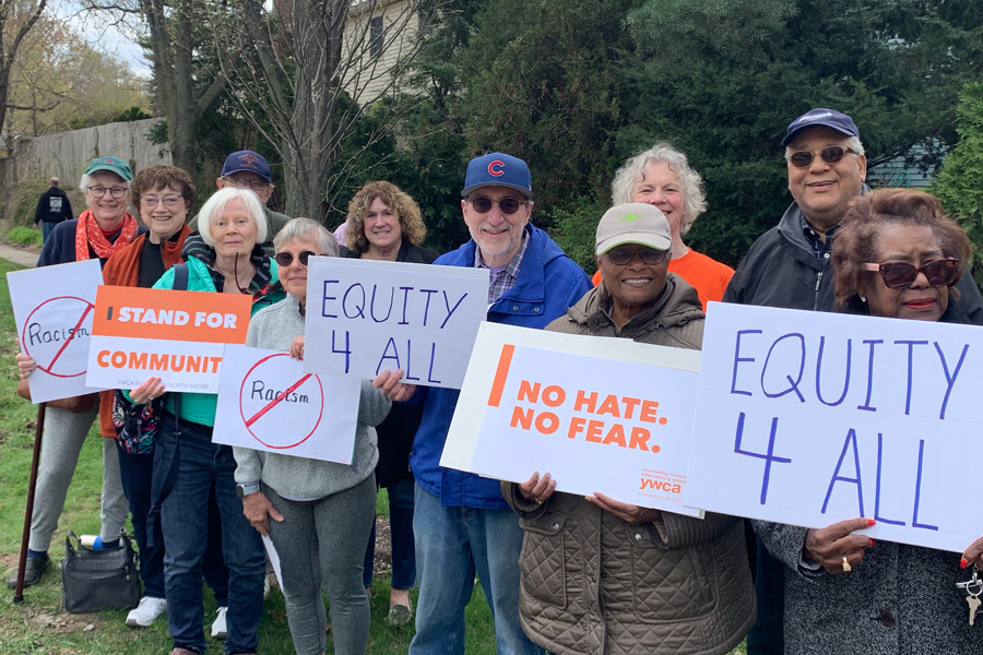Members of Evanston episcopal churches and Interfaith Action of Evanston stand along Ridge Avenue. The participants created signs to show support for the YWCA's Stands Against Racism event.