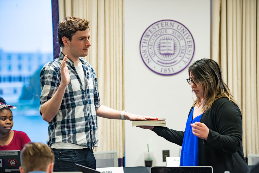 Weinberg junior Henry Molnar, left, is sworn in by former chief of staff Julia Shenkman, right. Molnar will focus on reforming ASG's image with the student body, he said.