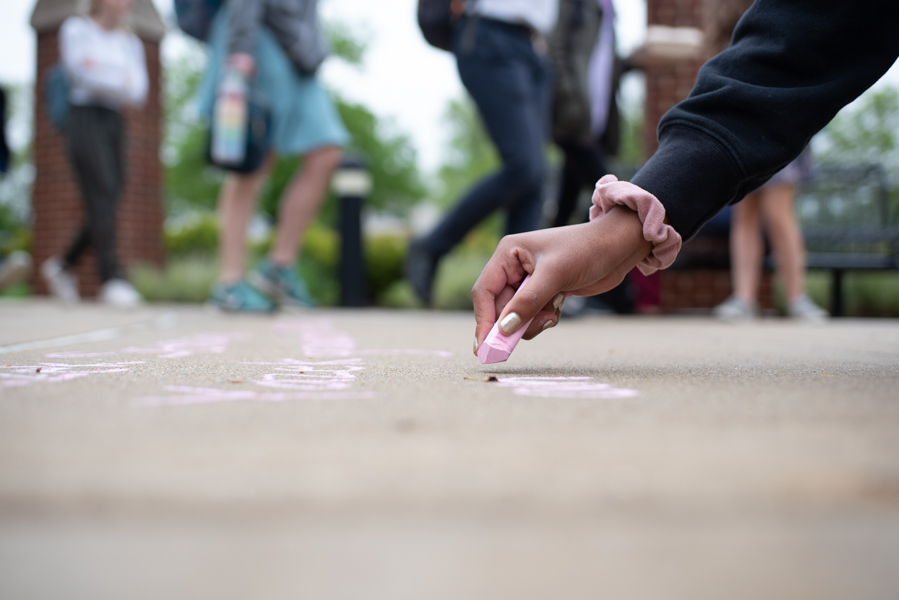 A+student+writes+out+a+message+in+chalk.+The+demonstration+also+consisted+of+a+short+rally+and+eight+minutes+of+silence+during+which+students+lied+on+the+ground.