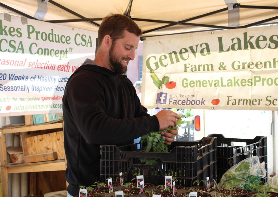 Corban Koster of Geneva Lakes Produce sorts through vegetables he put on display for customers at the Downtown Evanston Farmers' Market.