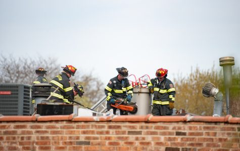 Evanston firefighters use a fire rescue saw and large Halligan bars to open the roof of the apartment building at 1740 Hinman Ave. EFD responded to a fire at the complex Wednesday at 4 p.m.