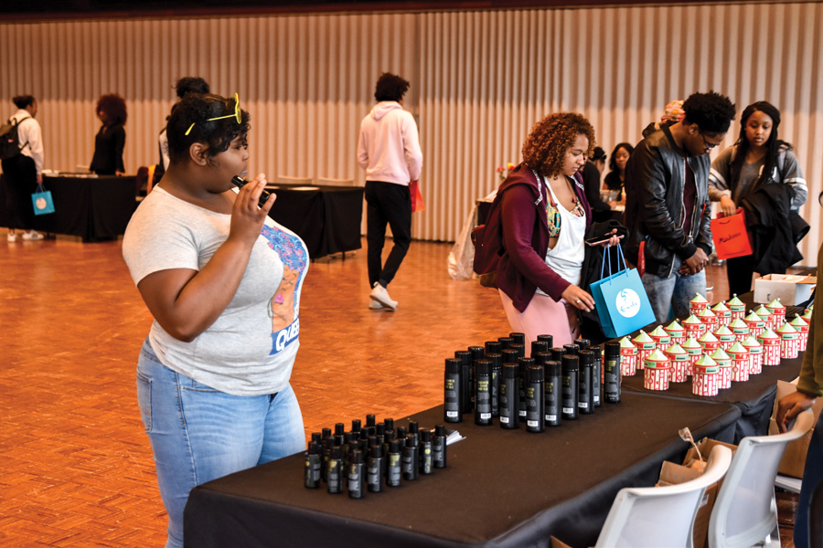 Students line up to receive samples at the Black Hair Expo. The event was held Sunday in Louis Room and showcased vendor booths and free hair care products.