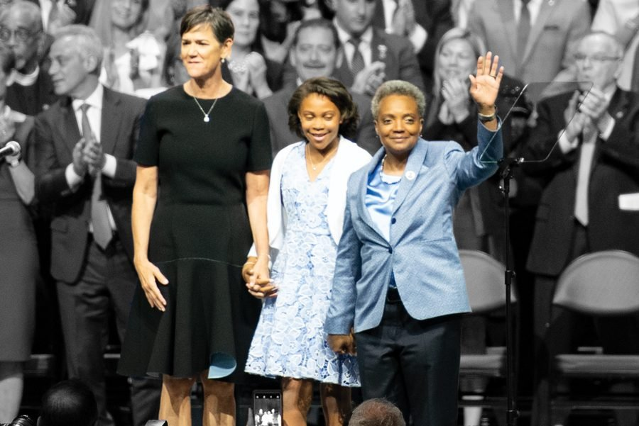 Mayor Lori Lightfoot waves to the crowd alongside wife Amy and daughter Vivian. She is the first black woman and openly gay mayor.