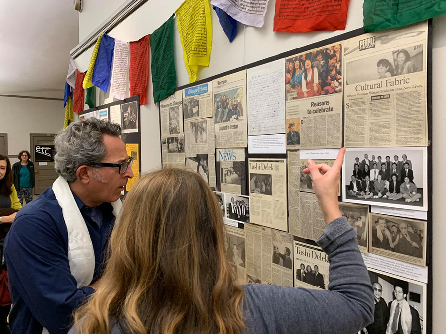 "Exhibit-goers browse newspaper clippings from the the period when the Tibetan refugee community began to settle in Chicago. In addition to the articles, the ""Tibetans in Chicago: A story of resilience and success"" exhibit includes portraits, photos and letters."