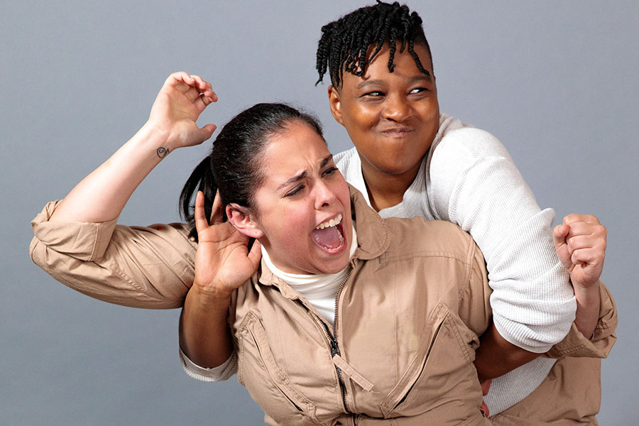 Actors from Women of 4G, opening August 1 at The Factory Theater, perform a fight.