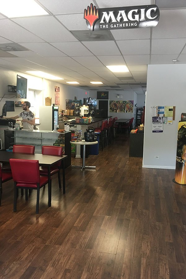 Eli Klein, owner of Evanston Games and Cafe, orders food to prepare to open the store. Evanston Games and Cafe serves the community by offering a variety of board games and weekly tournaments in a casual setting.