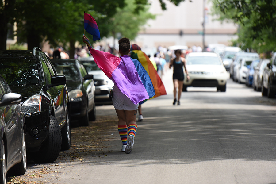 Attendees along the parade route draped themselves in flags representing different genders and sexualities. Above, the pink, purple and blue flag symbolizes bisexuality.