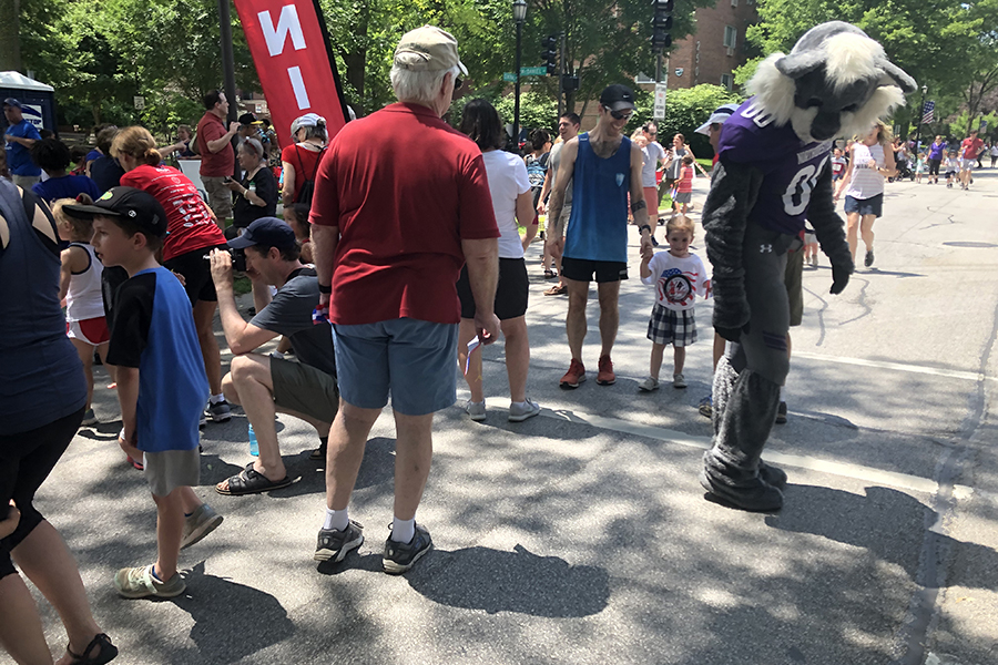 Six-year-old Evanston resident Abel McKenney and his father, Doug McKenny. The two approached Willie the Wildcat at the finish line of the Kids Fun Run.
