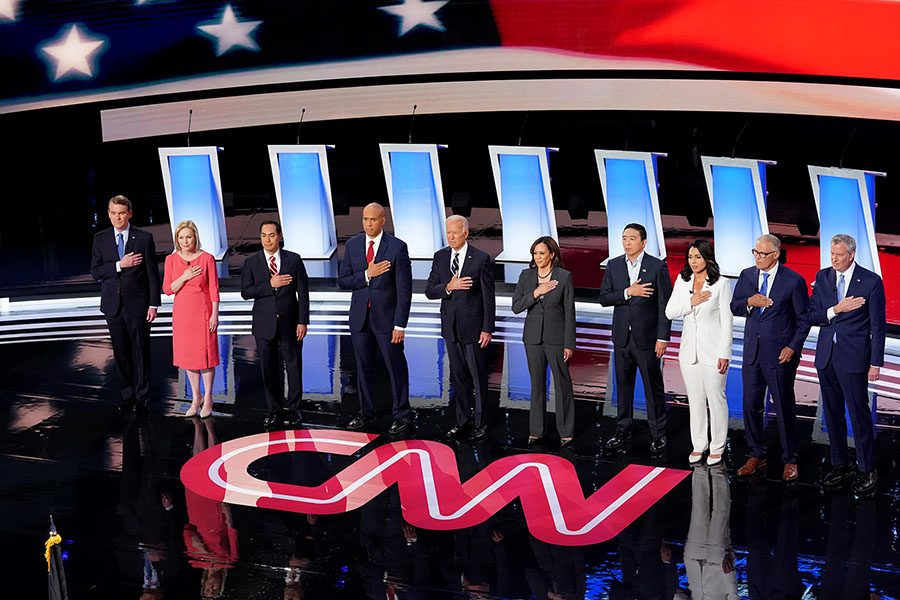 Candidates listen as the national anthem plays before the second night of debates in Detroit. The presidential hopefuls discussed a range of issues like healthcare, race and climate change.