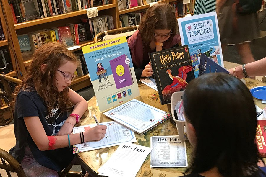 Kids fill out Harry Potter-themed word puzzles at a special event hosted by Bookends & Beginnings on Wednesday evening.
