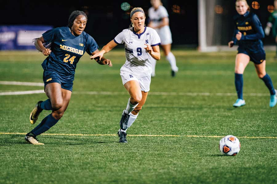 Kayleigh Stahlschmidt dribbles between two defenders. The junior forward said NU's newcomers are already a big part of this year's team.