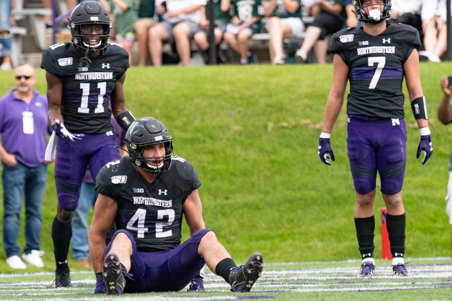 A group of Northwestern defenders show frustration in the end zone following a play. The Wildcats fell 31-10 to Michigan State in a disappointing loss to open Big Ten play.