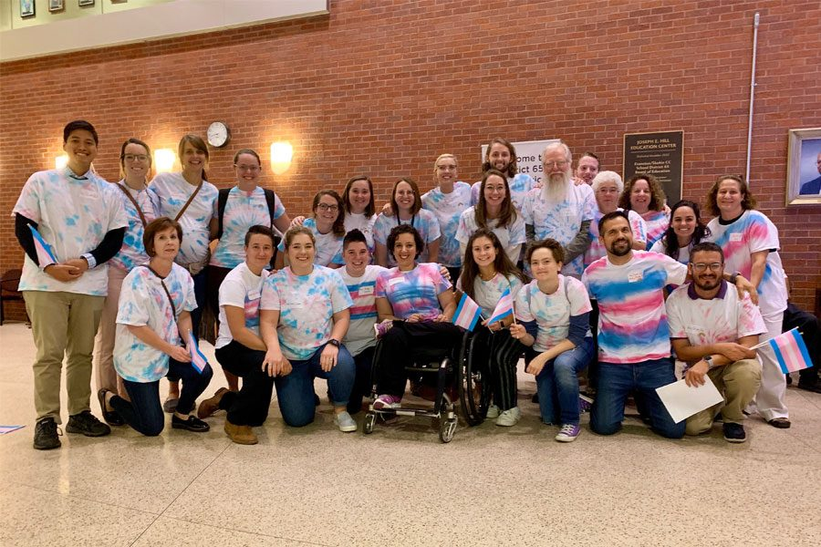 D65 community members at the board meeting. Employees, parents and alumni dressed pink, blue and white tie-dye and carried transgender flags.