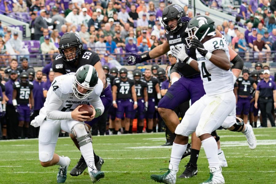 Brian+Lewerke+funs+away+from+a+Northwestern+defender.+Lewerke+earned+his+first+win+over+the+Wildcats+on+Saturday.