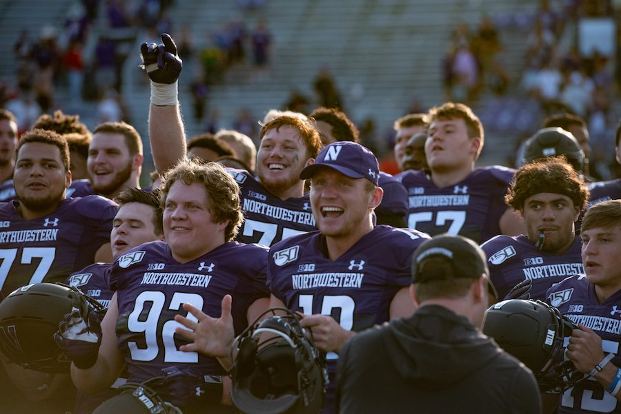 Jason+Whittaker+%28hat%29+celebrates+after+Northwestern+defeated+UNLV.+Whittaker+now+wears+No.+13+after+wearing+No.+7+and+No.+85.