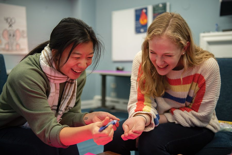 Lucy Yang and Chloe Cohen working on a poster for the Chicago Marathon. Lucy Yang said it can be difficult to find and retain engaged members who do not already identify with the marginalized group in need.