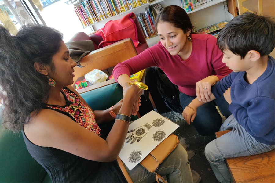 Henna artist Shruti Vijay (left) applies mehendi to Ankita Bhan and her son. The celebration was held Saturday at the CAMS branch of Evanston Public Library.