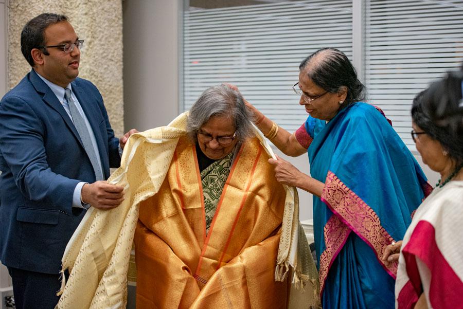 Sen. Ram Villivalem (D-Skokie) (left) and Dharani Villivalem (right) honor Ela Gandhi (center) Thursday at Skokie Public Library.
