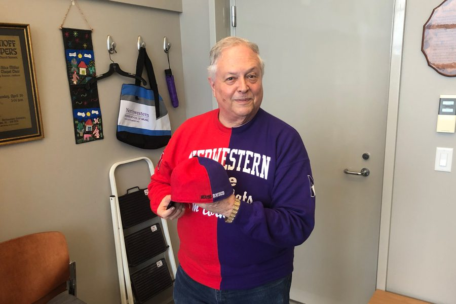 Kurt Hansen holds his House Divided hat and Nebwestern T-shirt. The Bienen professor became a faculty member in 1991.
