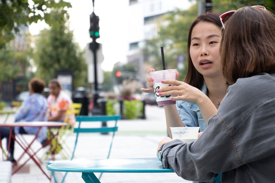 """Northwestern students Molly Liu and Irem Ozturan enjoy Colectivo smoothies in downtown Evanston's vibrant Fountain Square. A recent PwC report listed Evanston's vibrancy as an example of """"hipsturbia"""": a national trend of revitalized suburban centers."""