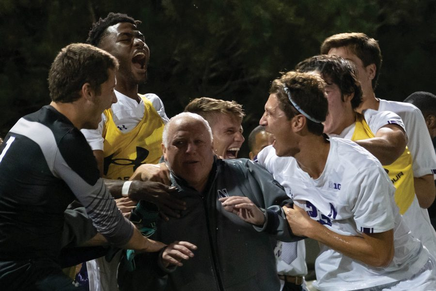 Ugo Achara Jr. celebrates with Coach Lenahan after his 300th win. The freshman forward scored his second career goal Tuesday.