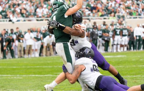Former defensive lineman Jordan Thompson takes down Michigan State quarterback Brian Lewerke. Thompson is one of many seniors whose presence the Wildcats have missed this season.
