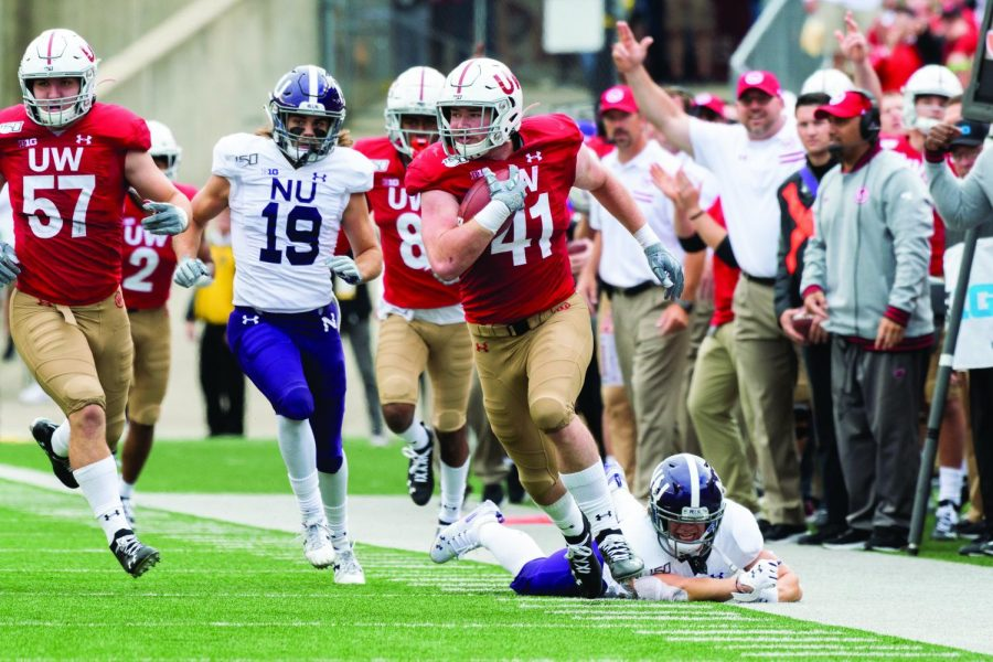 Northwestern players chase after Wisconsin's Noah Burks as he races to the end zone for a pick six. The Wildcats have struggled to a disappointing 1-5 start this season.