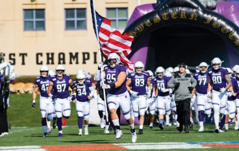 Alex Miller leads NU onto the field. The senior defensive lineman plays alongside his brother Samdup.