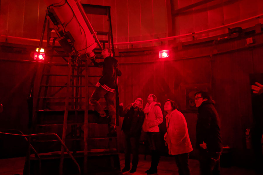 People stand in line under the red glow of the Dearborn Observatory to look through a telescope at the moon on Friday during the CIERA Astronomer Evening. Attendees could also attend a lecture by different researchers about their work in astronomical fields.