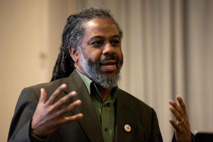 Dino Robinson talks at NCDC dialogue Monday about sundown towns in Illinois, redlining in Evanston and housing segregation at Northwestern.
