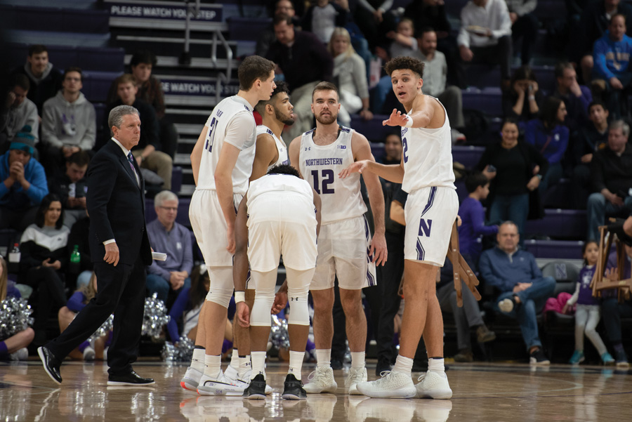 A bunch of Wildcats huddle before a play. Northwestern will look to set its rotation in the last few games before Big Ten play