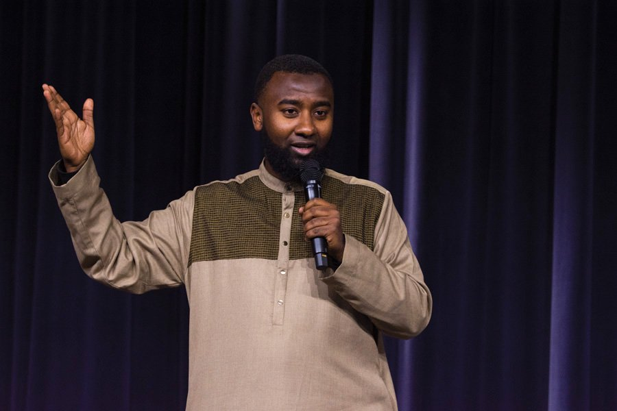"Boonaa Mohammed speaks to an audience at the McCormick Foundation Center on Thursday. He performs a spoken word poem titled ""Signs"" and sings along to a background vocal track of his song ""99 Beautiful Names."""