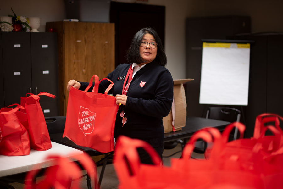Capt. Mary Kim prepares a Thanksgiving Food Box for for one of this season's bell ringers. The new leader of the Salvation Army Evanston Corps said she hopes to bring joy to the holiday season through these brightly colored bags of thanksgiving essentials which will be paired with entire turkeys for local residents.