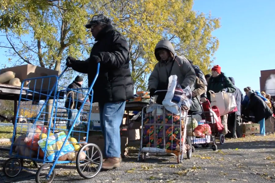 People line up for groceries in Evanston. The city has not changed its holiday services despite state-wide budget cuts.